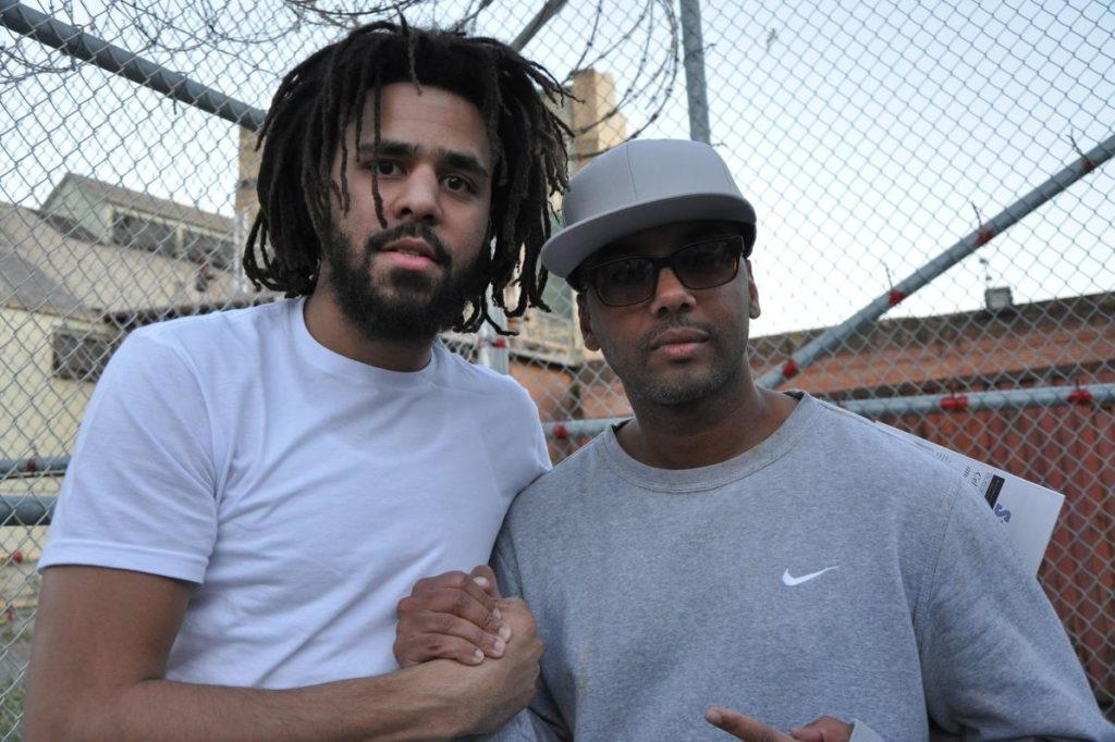 """This undated image shows music artist J Cole, left, with incarcerated Swedish music producer David Jassy at San Quentin State Prison in California. Jassy, whose sentence was commuted by California Gov. Gavin Newsom this year, produced an album """"San Quentin Mixtape, Vol. 1,"""" featuring work from 17 incarcerated rappers."""