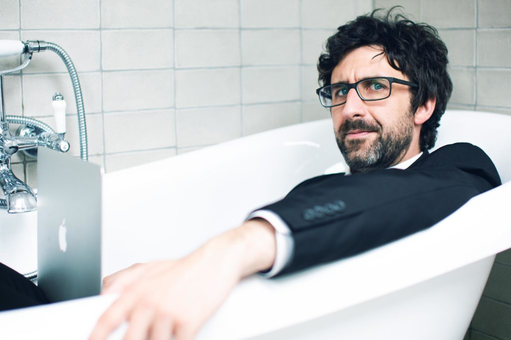Mark Watson sitting in a white bath tub with his suit on and a laptop on his lap