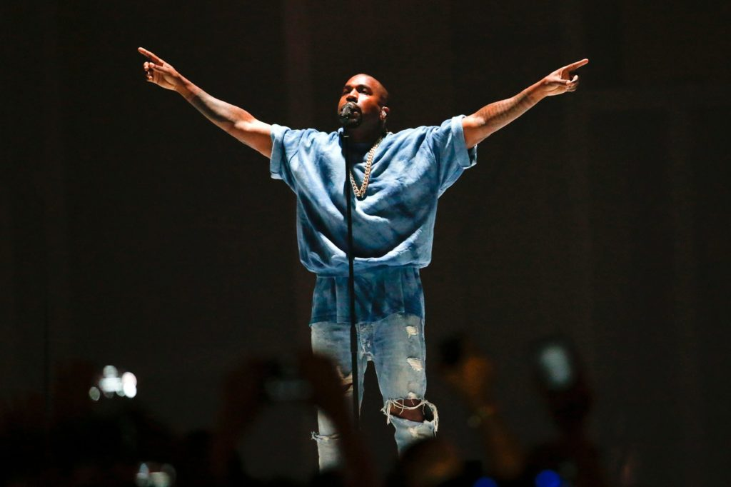 Kanye West performing with his hands lifted like a bird toward the sky