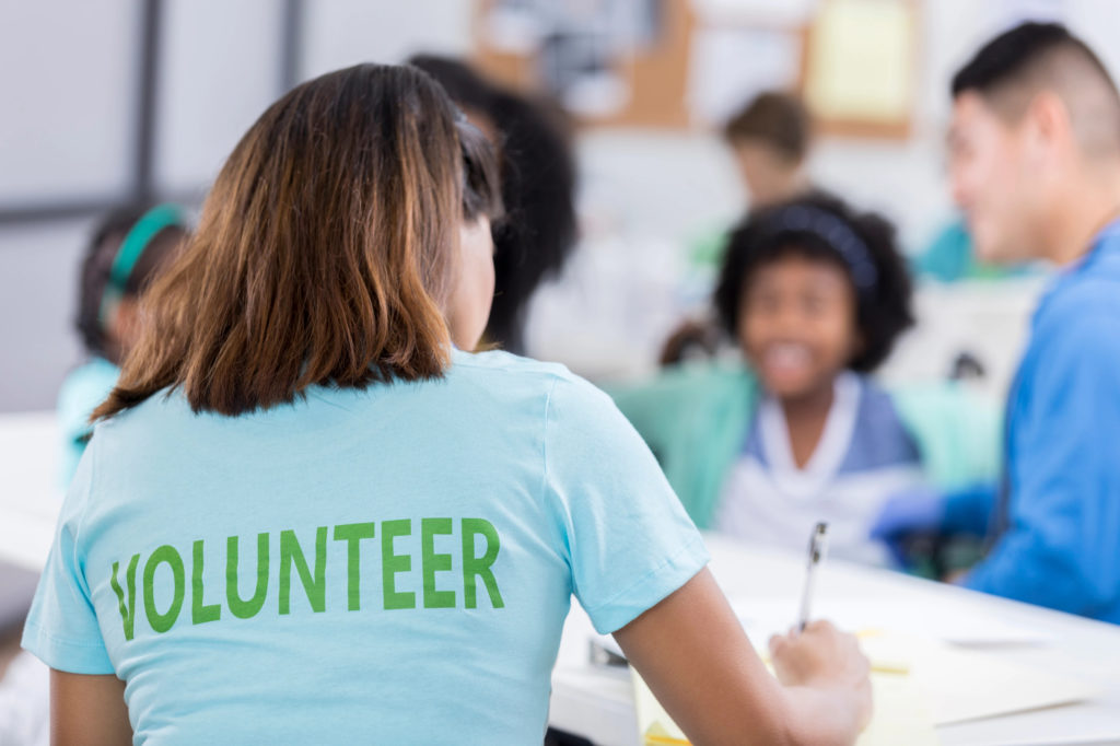 A woman wearing a t-shirt that says Volunteer on the back