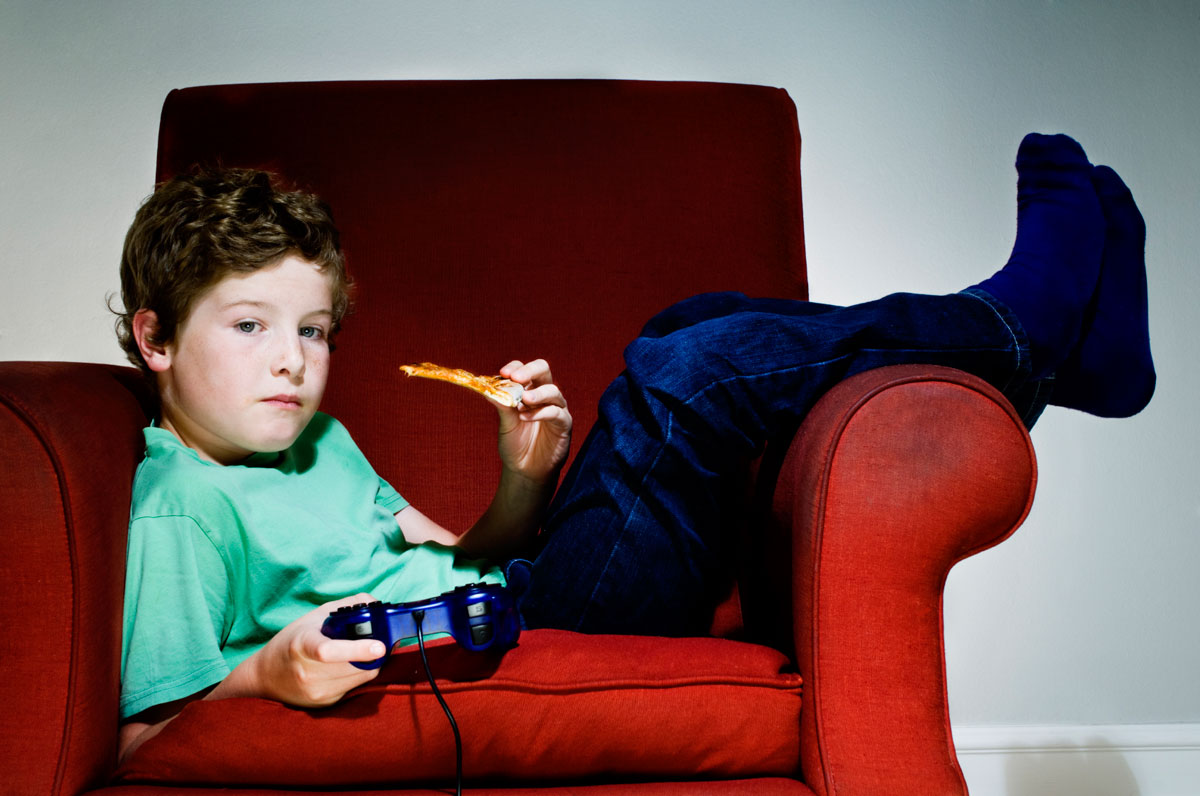 Boy laying in an armchair with a piece of pizza and a console