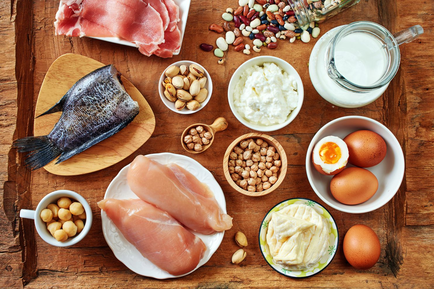 A wooden table with protein-rich foods including eggs, chicken, milk, nuts, beans, and fish