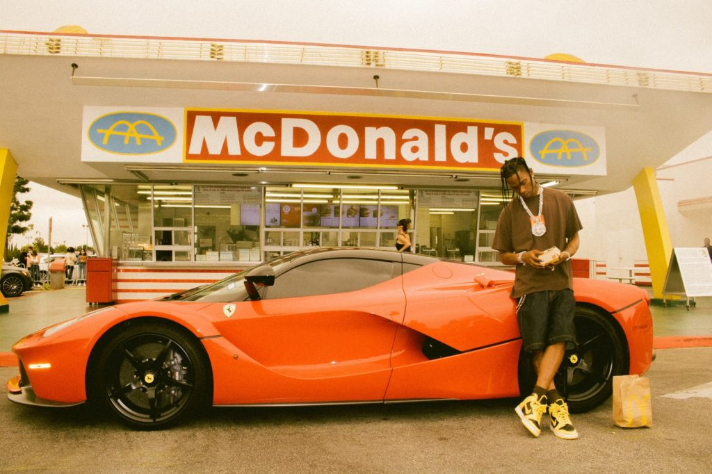 Rapper Travis Scott leaning on a luxury car parked in front of McDonald's