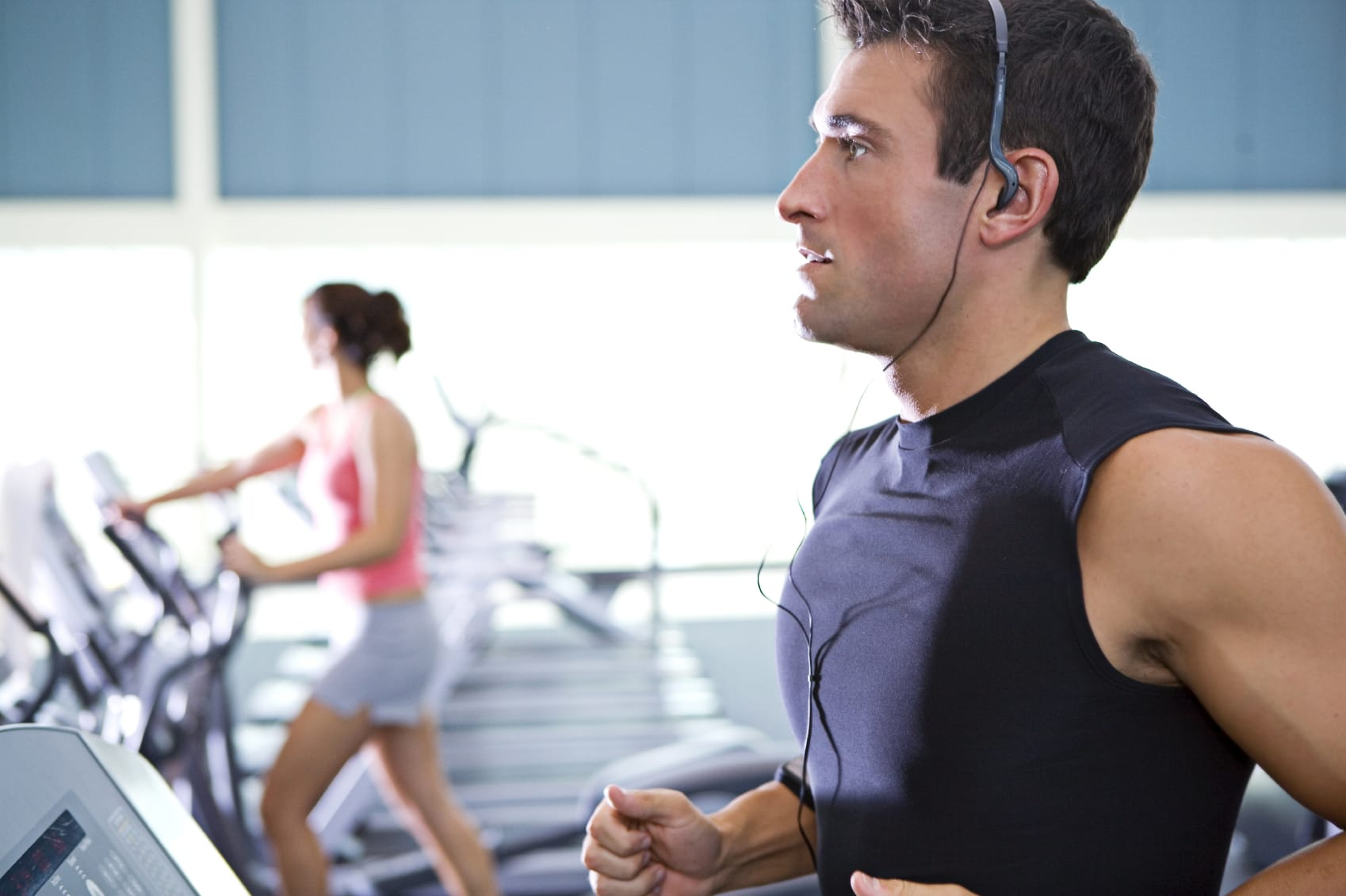 man with headphones on a gym workout, woman in the background