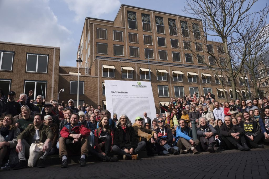 Climate activists pose outside the Shell headquarters, rear, in The Hague, Netherlands