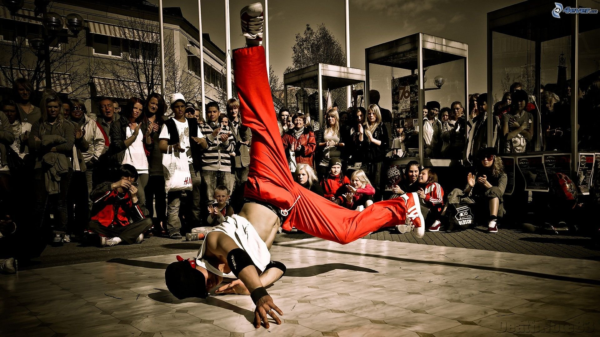 Young man during a breakdancing routine with a large audience on the street