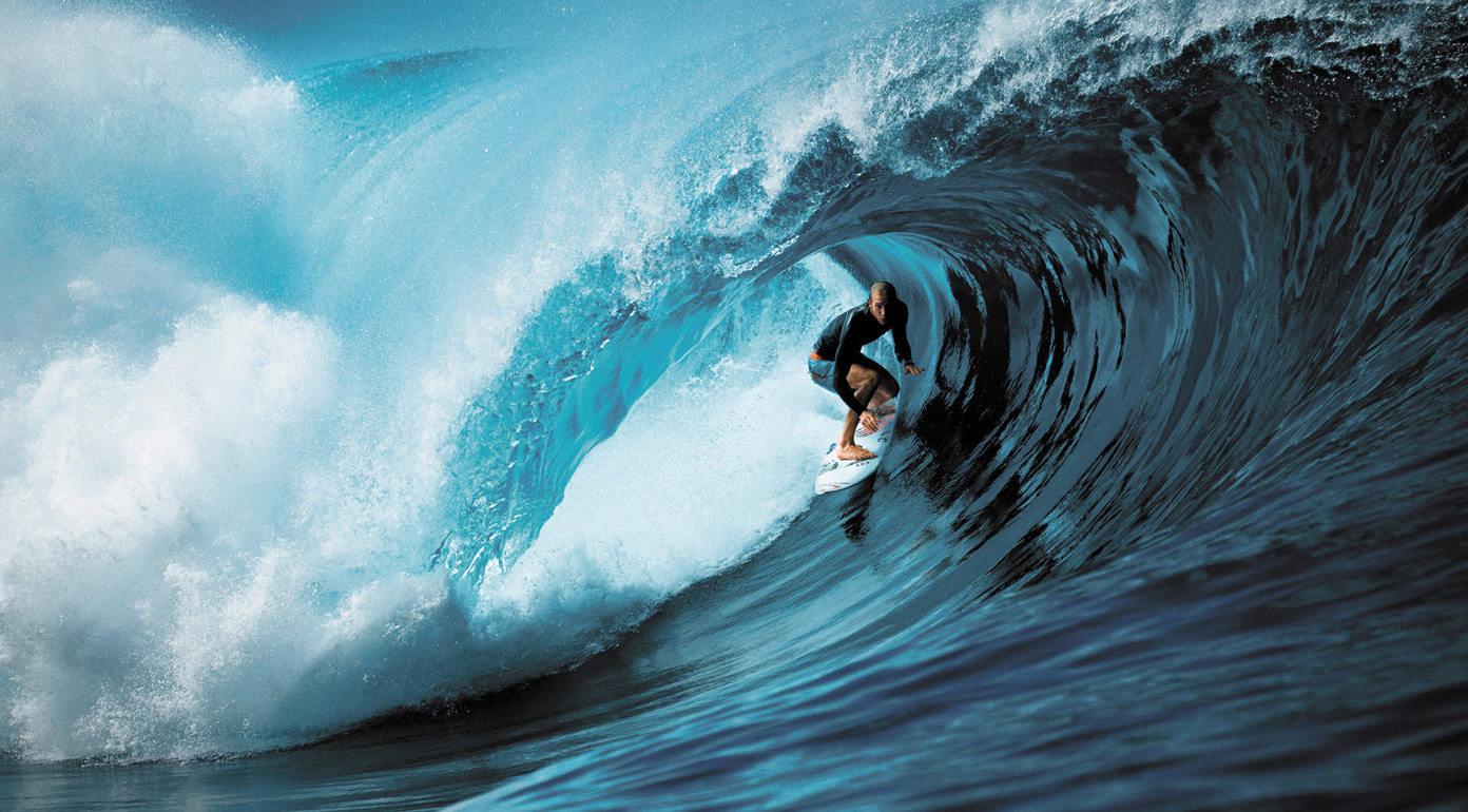 A surfer under the tip of a wave
