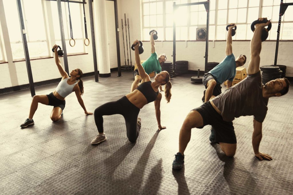 Athletes exercising with weights on floor